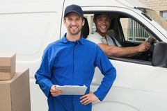 Delivery driver checking his list on clipboard with client Royalty Free Stock Photos