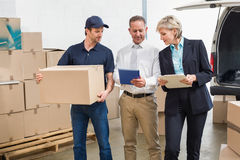 Delivery driver checking his list on tablet with managers Stock Image