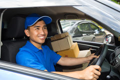 Delivery driver driving with parcels on seat. Postal activities Royalty Free Stock Image