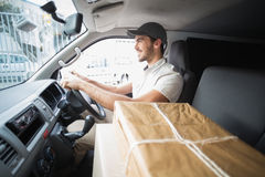 Delivery driver driving van with parcels on seat Stock Photo