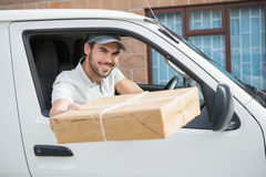 Delivery driver offering parcel from his van Royalty Free Stock Photos