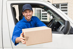 Delivery driver offering parcel from his van. Outside the warehouse Stock Images