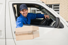 Delivery driver offering parcel from his van Royalty Free Stock Photo