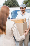 Delivery driver passing parcels to happy customer Royalty Free Stock Photos
