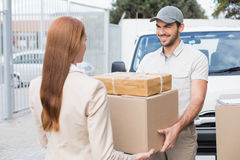 Delivery driver passing parcels to happy customer Stock Photo