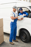 Delivery driver showing customer where to sign Stock Photography