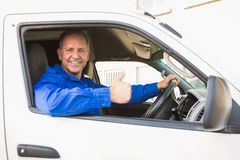 Delivery driver showing thumbs up driving his van. Outside the warehouse Stock Image