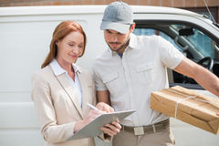 Delivery driver showing where to sign to customer stock photography