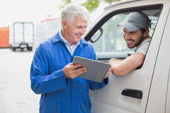 Delivery driver smiling at camera with customer Royalty Free Stock Images