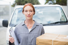 Delivery driver smiling at camera by her van holding parcel Royalty Free Stock Photo