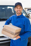 Delivery driver smiling at camera by his van holding parcel Royalty Free Stock Images