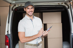 Delivery driver smiling at camera beside his van Royalty Free Stock Photography