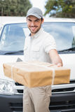 Delivery driver smiling at camera by his van offering parcel Royalty Free Stock Photos