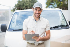 Delivery driver smiling at camera by his van Royalty Free Stock Photo