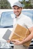 Delivery driver smiling at camera by his van Royalty Free Stock Photography