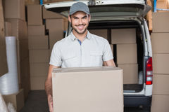 Delivery driver smiling at camera holding box Stock Photography