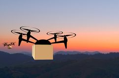 Delivery drone with the package. Against the background of mountains and evening light. Fast and convenient transportation concept stock images
