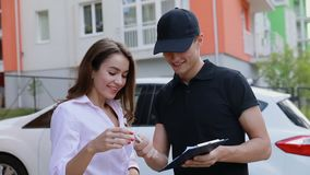 Delivery. Express Courier Delivering Package To Client Home. Delivery. Express Courier Delivering Package To Client, Woman Signing Delivery Documents Outdoors stock footage