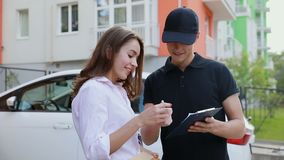 Delivery. Express Courier Delivering Package To Client Home. Delivery. Express Courier Delivering Package To Client, Woman Signing Delivery Documents Outdoors stock video