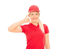 Delivery girl making call sign with her hand Royalty Free Stock Photo