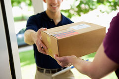 Delivery: Giving Package to Home Owner. Series with with a delivery men dropping off flowers, boxes, balloons, etc. to a residential suburban home Stock Photos