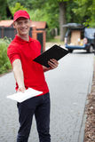 Delivery guy giving a packet Royalty Free Stock Images