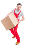 Delivery guy holding big cardboard box and moving Stock Images