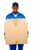 Delivery guy holding big parcel and smiling Royalty Free Stock Photography
