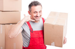 Delivery guy holding box and making calling gesture Stock Photography