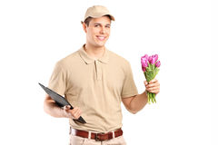 Delivery guy holding a bunch of flowers and a clipboard Stock Photos