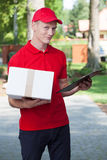 Delivery guy holding a package Stock Photography