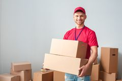 Delivery guy isolated on white wall standing holding boxes looking camera cheerful stock photos