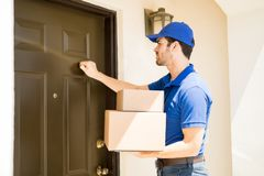 Delivery guy knocking on the door. Closeup of a young man delivering a few packages to a house and knocking on its door Royalty Free Stock Photo