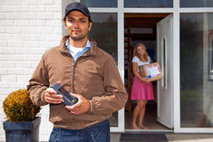 Delivery guy with Wireless PIN machine. Delivery guy, holding a wireless pin machine walking away from a house, where a women stands in the doorway, with the Royalty Free Stock Photography