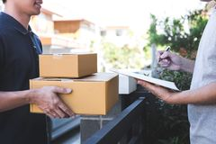 Delivery mail man giving parcel box to recipient, Young man signing receipt of delivery package from post shipment courier at home royalty free stock photography