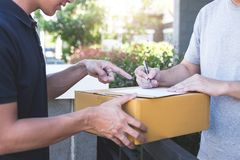 Delivery mail man giving parcel box to recipient, Young man signing receipt of delivery package from post shipment courier at home royalty free stock images