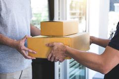 Delivery mail man giving parcel box to recipient, Young owner accepting of cardboard boxes package from post shipment, Home. Delivery mail men giving parcel box stock image