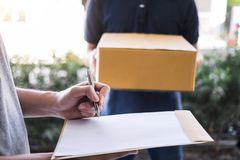 Delivery mail man giving parcel box to recipient, Young man signing receipt of delivery package from post shipment courier at home stock photography
