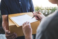 Delivery mail man giving parcel box to recipient, Young man signing receipt of delivery package from post shipment courier at home royalty free stock photos