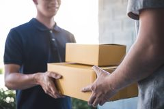 Delivery mail man giving parcel box to recipient, Young owner accepting of cardboard boxes package from post shipment, Home. Delivery mail men giving parcel box stock photo