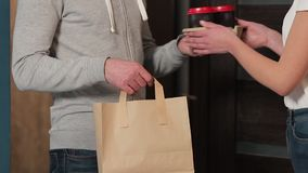 Delivery, mail and people concept - happy man delivering coffee and food in disposable paper bag to customer home and. Taking payment stock footage
