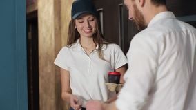 Delivery, mail and people concept - happy woman delivering coffee and food in disposable paper bag to customer home and. Taking payment stock video