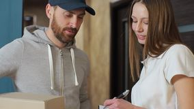 Delivery, mail, people and shipping concept - happy man delivering parcel boxes to customer home. Giving clipboard for signature at home stock video footage