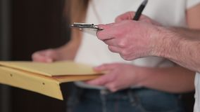 Delivery, mail, people and shipping concept - happy woman delivering parcel boxes to customer home. Giving clipboard for. Signature at home stock footage