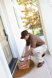 Delivery Man. A young delivery man delivering a package to a house stock photo