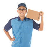 Delivery man. Delivery person delivering package smiling happy in blue uniform. Handsome young Asian man professional courier isolated on white background stock photography
