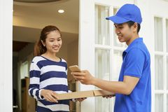 Delivery man accepting payment via mobile app royalty free stock image
