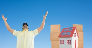Delivery man with arms raised against house and parcels. Digital composite of Delivery man with arms raised against house and parcels Stock Photo