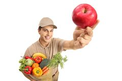 Delivery man with a bag of groceries and an apple. Isolated on white background stock photography