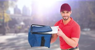 Delivery man with blue bag against blurry street with flares. Digital composite of Delivery man with blue bag against blurry street with flares Stock Photos